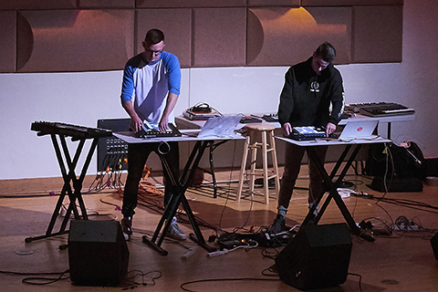 Two men with drum machines perform on stage during an event